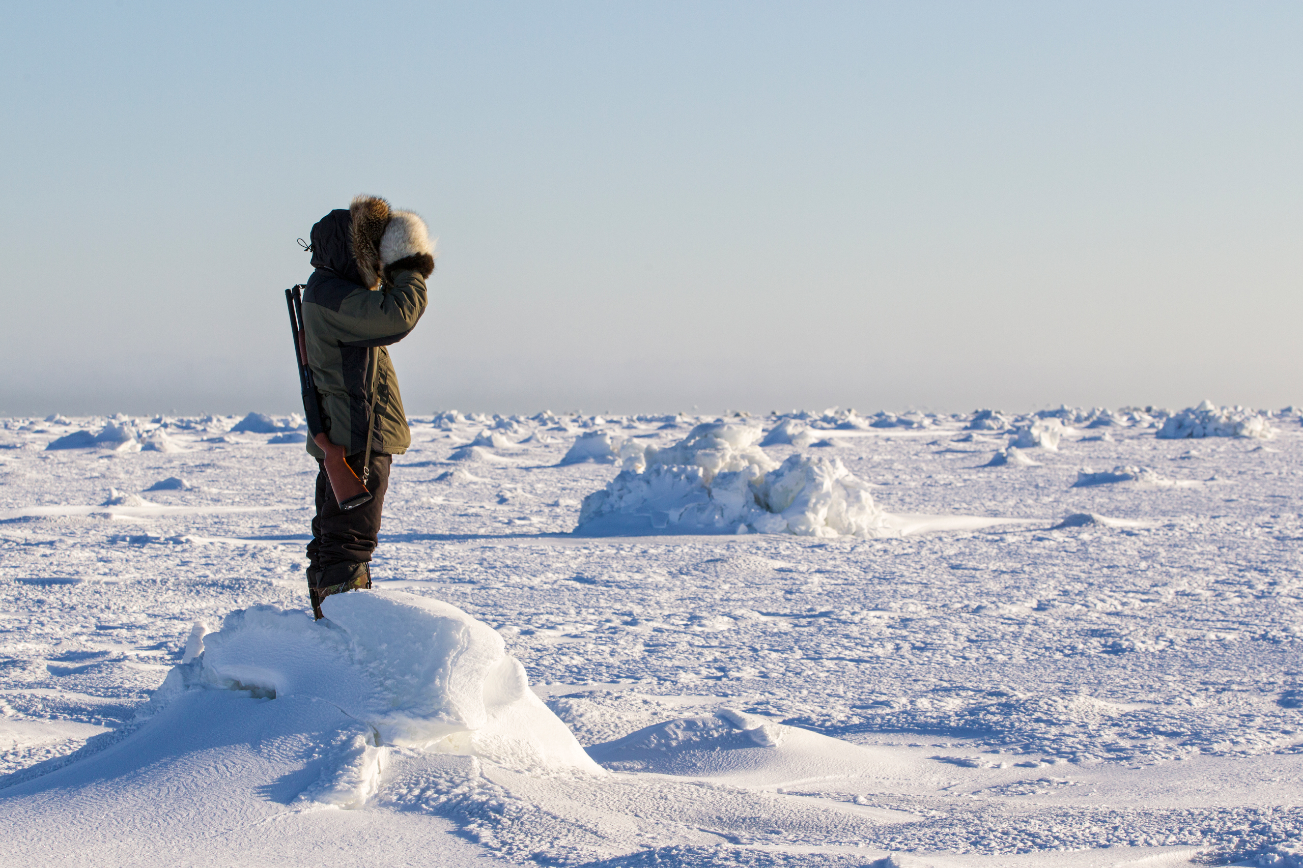 Inuit man scanning ice for polar bears, west coast Hudson Bay, south of Arviat, Nunavut, Canada